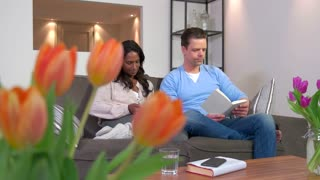 Married interracial couple using ipad digital tablet and reading book, people relaxing on couch at home. Wifi technology for internet, email, lifestyle, relaxation, fun with husband and wife on sofa