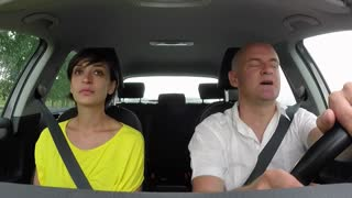 Married white couple on road trip, happy people traveling by car on the street, man driving vehicle with woman. Angry husband and wife fighting with another driver. Road rage