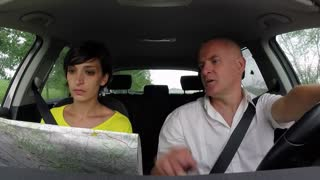 Married white couple on road trip, happy people traveling by car on the street, man driving vehicle with woman. Husband and wife using map and road atlas for travel directions