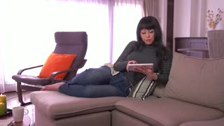 Mature Japanese woman with ipad, middle aged Asian lady using digital tablet on sofa in living room at home. Wi-fi technology for social network, internet, email, lifestyle, relax