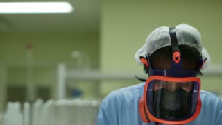 Medicine, science, and pharmaceutical laboratory with scientist wearing mask and looking at camera while working. Sequence
