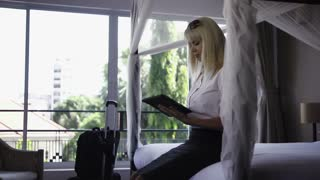 Mid adult caucasian businesswoman typing on tablet pc in hotel room during business travel. Medium shot
