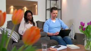 Mixed race heterosexual couple, people on sofa, marriage relationship with young husband and wife. Angry man and woman arguing, fighting at home. Domestic problems, loud talking and screaming