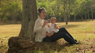 Mother Playing Soap Bubbles With Little Baby Daughter In Park On Grass