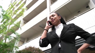 Multiethnic Young Woman Talking On Telephone Smartphone Near Office Skyscrapers