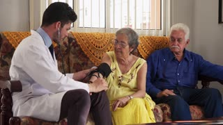 Old Woman During Visit With Young Doctor In Hospital