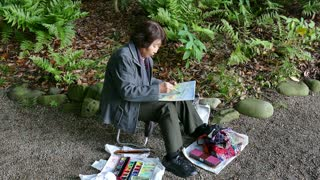 Old woman painting natural landscape at Koishikawa Korakuen Gardens, Tokyo, Japan, Asia. Elderly people, seniors, senior lady in city park. Japanese traditional culture, art, painter, artist
