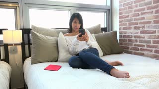 People and technology at home, Korean female student with cell phone, young Asian woman texting on mobile telephone, girl on bed sending text message with smartphone