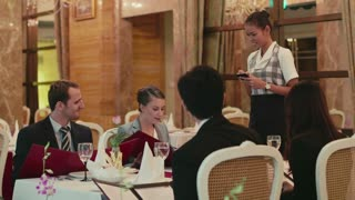 People eating, dining at hotel restaurant, leisure and fun, friends, men and women, couples, husband and wife having dinner, talking and laughing. Portrait of asian girl, waitress at work, writing order, looking at camera