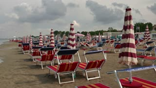 People on holidays in Italy, tourists on summer vacations. Italian coast in Igea Marina on Adriatic Sea. View of sandy beach with umbrellas and sunbeds at sunset