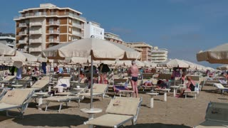 People relaxing on holiday in Italy, families and tourists on summer vacation. Italian coast in Igea Marina on Adriatic Sea. Sandy beach with hotels near Rimini, Emilia Romagna