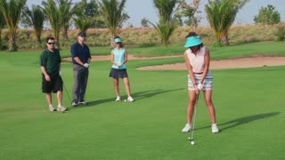 People, sport, leisure activities, recreation and lifestyle, golf in country club during summer holidays. Asian woman playing golf near hole, group of friends watching