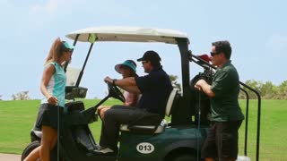 People, sport, leisure activity, recreation and lifestyle, group of friends talking and having fun on golf cart in club during summer holidays. Portrait of men and women looking at camera