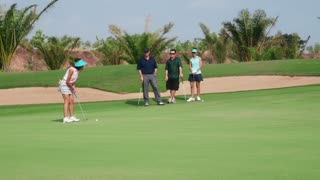 People, sports, leisure activities, recreation and lifestyle, golf in country club during summer holidays. Asian woman hitting ball with iron in golf course near hole, friends watching