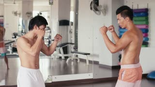 People training, working out, doing exercise in gym and fitness club, sport and martial arts for wellness and well-being. Portrait of asian men fighting and simulating extreme combat, karate, kung fu, kickboxing