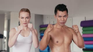 People training, working out, doing exercise in gym and fitness club, sports and martial arts. Personal trainer and girl, woman doing kickboxing for self-defense, portrait looking at camera