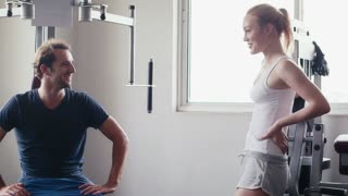People training, working out, doing exercise in gym and fitness club, sports, body-building for wellness and well-being. Friends, man and woman talking and relaxing near fitness machine