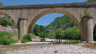 People with kayak on river Tarn in La Malene, southern France. Old bridge on the Gorges du Tarn, French tourists and families enjoying summer day, swimming, doing picnic on vacation