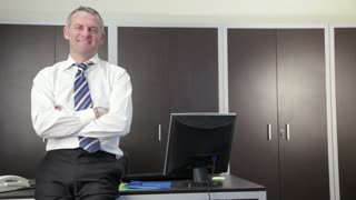 Portrait of businessman, manager smiling and looking at camera in office. Dolly shot