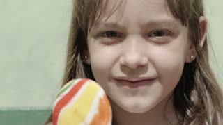 Portrait of cute little girl with candy bar smiling and looking at camera