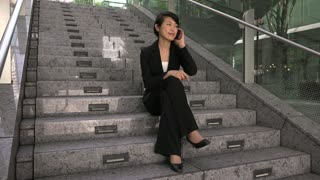Portrait of happy beautiful Japanese manager speaking on cell phone, smiling at camera. Asian businesswoman, successful girl, busy woman talking with smartphone, sitting on the stairs. Slow motion
