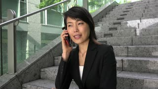 Portrait of happy beautiful Japanese manager talking on telephone, smiling at camera. Asian businesswoman, successful girl, busy woman talking with smartphone, sitting on steps. Slow motion