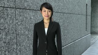 Portrait of happy pretty Japanese female manager looking at camera. Young Asian businesswoman, confident girl, elegant woman smiling near office building. Career, success. Slow motion