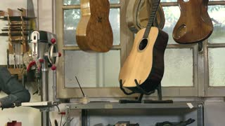 Portrait of Italian adult man working as craftsman in shop with tools, bass, guitar and musical instruments
