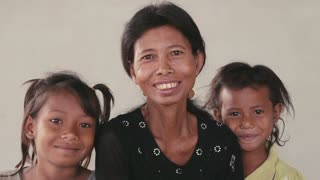 Portrait of real Asian people, with emotions and feelings, looking at camera. Happy family with woman and little girls from Cambodia, Southeast Asia smiling