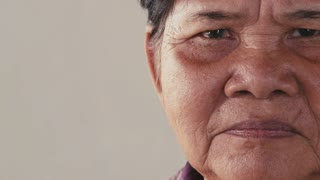 Portrait of real Asian people, with emotions and feelings, looking at camera. Sad elderly woman from Cambodia, Asia