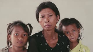 Portrait of real Asian people, with emotions and feelings, looking at camera. Sad family with mother and daughters from Cambodia, Asia