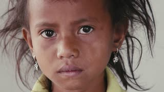 Portrait of real Asian people, with emotions and feelings, looking at camera. Sad female child from Cambodia, Southeast Asia