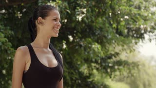 Portrait of two happy young women meeting and smiling after exercising in city park. Slow motion