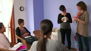 Pregnant woman, happy mom, mother, pregnancy. Lesson in hospital, class at maternity center. Teacher, midwife, counselor, doctor using doll to explain how to change diaper with baby, infant, newborn