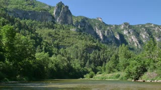 Quiet boat ride on river Tarn in southern France. View of the Gorges du Tarn, beautiful French natural landscape with canyons, mountains, forest, crystal clear water
