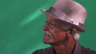Real Cuban people and feelings, portrait of serious senior black man looking away. Old latino grandfather with mustache and hat from Havana, Cuba talking