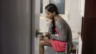 Sad, anxious, worried young woman using pregnancy test kit in bathroom at home. Maternity, motherhood, pregnant girl, parenthood