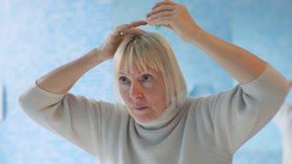 Senior woman at home, using hair lotion
