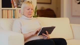 Senior woman at home, using ipad
