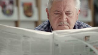Seniors and active retirement, old man with mustache reading newspaper in city library