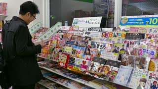 Shop, convenience store selling comics, press and manga magazines in Kyoto, Japan, Asia. Japanese man, young person, client, reader, customer reading