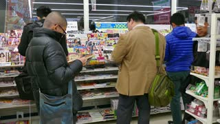 Shop, convenience store selling comics, press and manga magazines in Kyoto, Japan, Asia. Japanese men, people, clients, readers, customers reading