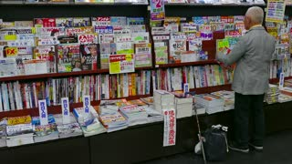 Shop, store selling comics, books, anime magazines in shopping mall, Hiroshima, Japan, Asia. Elderly Japanese man reading magazine, people, client, customer