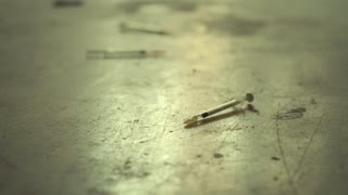 Social issues and substance abuse with syringes used for heroin and drugs on dirty floor. Low angle, dolly shot