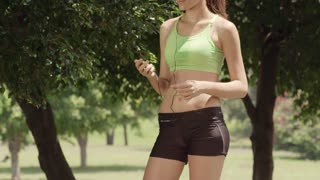 Sports activity, attractive young woman with mp3 player listening to tunes and doing fitness in city park