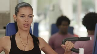 Sports activity, young man and woman exercising and working out in wellness gym. Rack focus