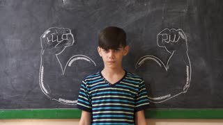 Strong Male Child Showing Muscles In Classroom At Lesson