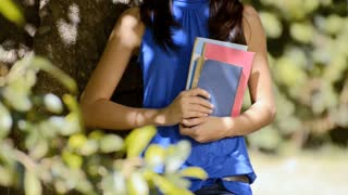 Students portrait at school, happy young woman smiling with college textbooks in park leaning on tree. Sequence
