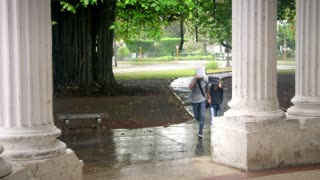 Students talking and smiling, boy and girl running in the rain during storm. Sequence