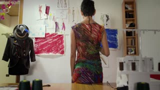 Success, young people and small business, hispanic woman at work as fashion designer and tailor, looking at sketches in atelier